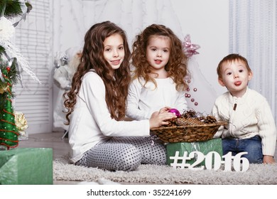 Little kids in comfortable home clothes sitting on floor in beautiful Christmas decorations. three little siblings decorating Christmas tree with fir-cone. New year preparation. Happy girls and boy