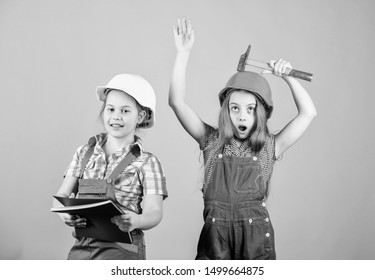 Little kids in helmet with tablet and hammer. Labor day. 1 may. small girls repairing together in workshop. Foreman small girls inspector. Repair. happy children. Future career. small girls.