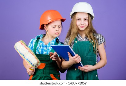 Little kids in helmet with tablet and roller. small girls repairing together in workshop. school project. Labor day. 1 may. Foreman inspector. Repair. Ready to repair your everything.