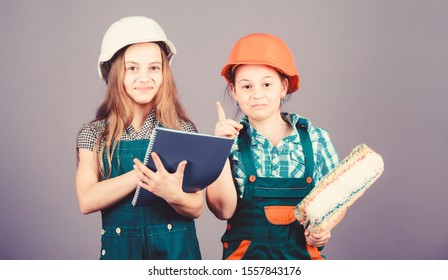 Little kids in helmet with tablet and roller. small girls repairing together in workshop. engineering idea. Labor day. 1 may. Foreman inspector. Repair. inspiration for creation. inspiration.