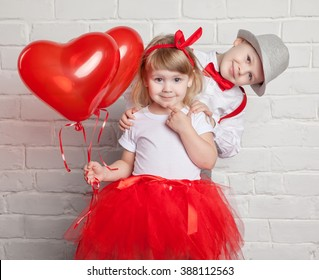 Little kids holding and picking up heart balloons. Valentine's Day and love concept, on white background