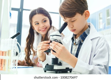 Little kids learning chemistry in school laboratory microscope experiment notes