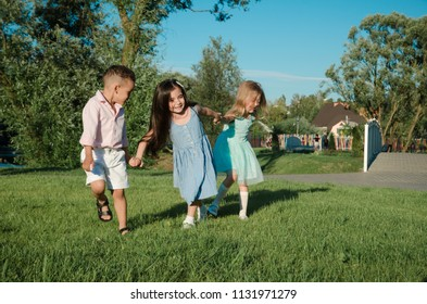 little kids playing around on the lawn. two girls and a boy