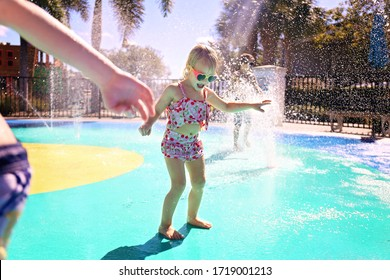 Little kids are playing outside in the water fountains at an outdoor splash pad park on a summer day.