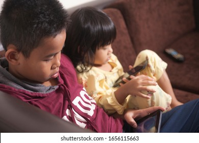 Little kids sister and brother siblings plays on gadget smart phone, phone addiction on children concept