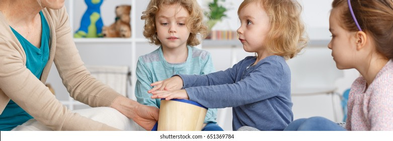 Little kids sitting in circle with a drum