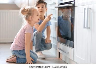 Little kids sitting near oven indoors