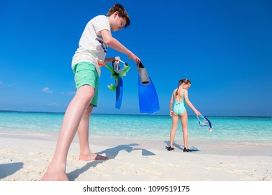 Little kids with snorkeling equipment on tropical beach having fun during summer vacation