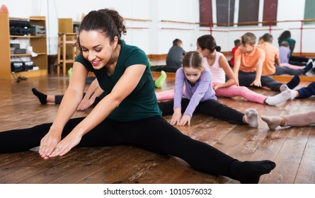 Little kids stretching with female teacher in dance hall