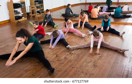 Little kids stretching with female teacher in dance class