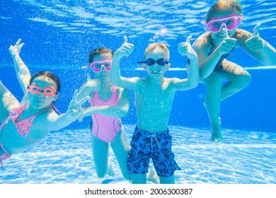 little kids swimming  in pool  underwater.
