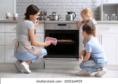 Little kids watching their mother bake cookies in oven indoors