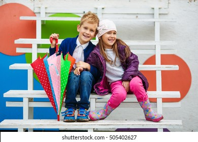 Little kids wearing stylish clothes on the wooden white stairs. Fashion kid concept.
