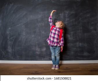 Little kindergarten child girl is measuring the growth against blackboard. Kid is ready to go to school.