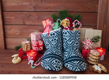 Little knitted boots with christmas presents and various cookies