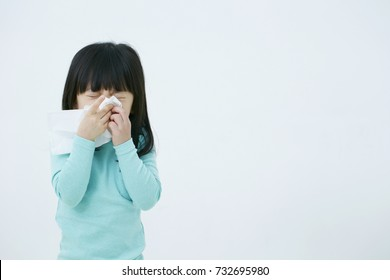 Little Korean girl blowing her nose