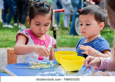 Little latin boy and girl making crafts.