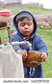 Little latin boy washing plate in the countryside.