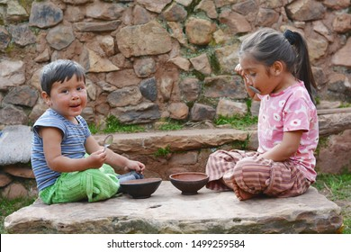 Little latin children sitting on the big stone and eating from rural bowl.