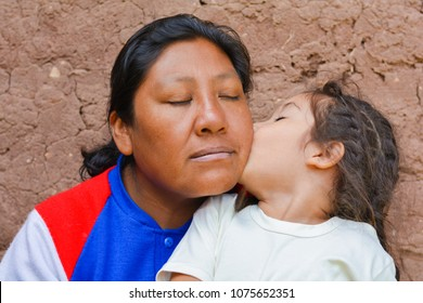 Little latin girl giving kiss to her mom.