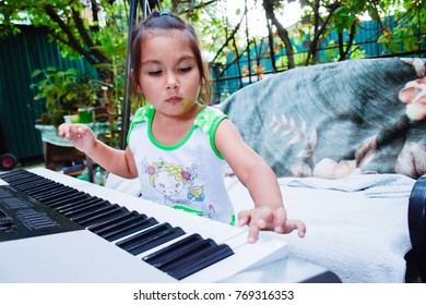 Little latin girl playing electric guitar on the backyard.
