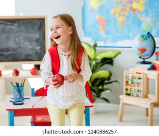 Little laughing blond girl standing near white desk with her red bag holding an apple in the spacious school classroom
