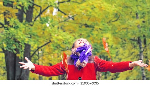 Little laughing pretty girl in red coat throws yellow leaves in autumn park.