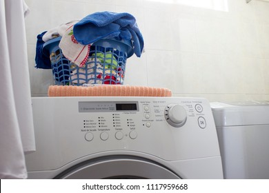 Little laundry area in a domestic house. There is a white shirt hanged at the left. In the center, a clean laundry basket with towels, rags and clothes, over a washing machine.