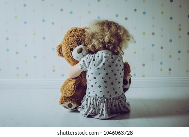 Little lonely curly haired girl crying in her room.