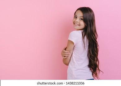 Little longhair girl standing backwards, turning his head to the camera over pink background