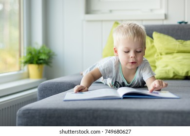 Little, lost in thought, three years old boy lying on his belly on the sofa, with open book in front of him.