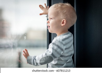 Little, lost in thoughts, and a bit irritated two years old boy standing by the window and thinking and waiting for something.