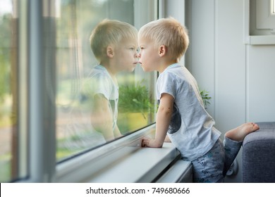 Little, lost in thoughts, and depressed three years old boy looking out  the window and thinking and waiting for something.