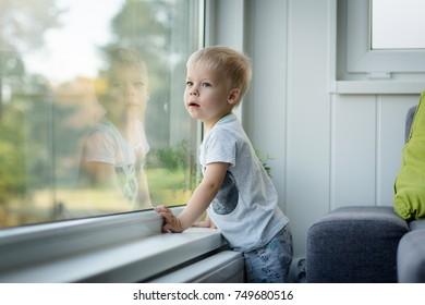 Little, lost in thoughts, and intrigued, three years old boy looking out  the window and thinking and waiting for something.