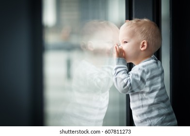 Little, lost in thoughts, and sad two years old boy sitting by the window and thinking and waiting for something.
