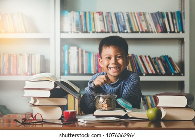 little lovely foreigner boy,student learning,playing ,smiles and counting,putting  money coins into the glass bottle  with fun and happy in school,library.