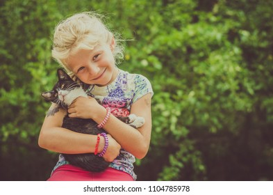 little lovely girl holding cute black and white cat