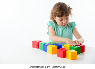 Little lovely girl plays with cubes