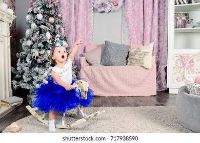 Little lovely girl swaying on the wooden horse, having fun and make faces. Pink Christmas interior with Christmas tree, fireplace and sofa on the background. Concept of Merry Christmas