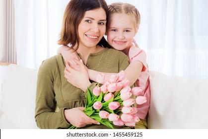 Little loving girl embracing her beatiful mother