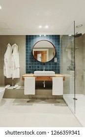 Little luxury bathroom with white bathrobes hanging on the wall. Round mirror, shower behind a glass wall. Gray wall blue tiles