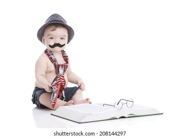 Little man.  Adorable little boy wearing a neck-tie, hat, and handle bar mustache next to a large book with glasses on top.  Isolated on white with room for your text.