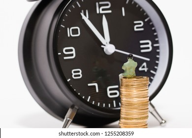 Little man sitting on gold coins and alarm clock