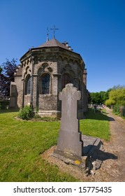 little medieval chuch with tombstone in the front