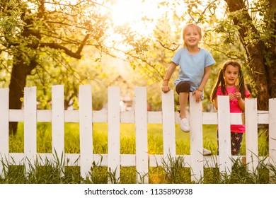 Little mischievous girl behind white fence. She smiles.