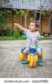 Little Mixed Race Asian Caucasian Boy On A Tricycle Pointing at his Friend