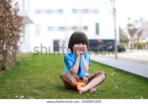 Little Mixed race Thai-German boy wearing Thai traditional dress sitting on the grass with water gun happy holiday celebration .songkran festival concept