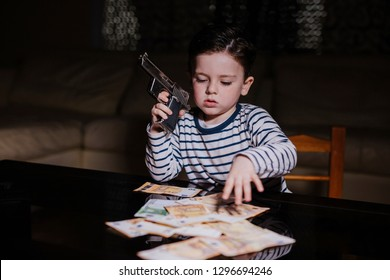 Little mobster with gun and money on the table