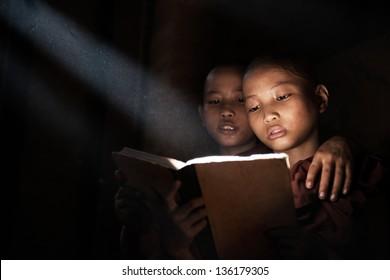 Little monks reading book inside monastery