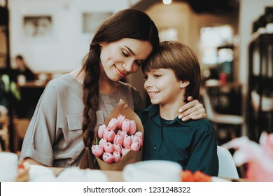 Little and Mother Happy Together. Boy Gift Mother Flowers. Love with Mother and Son. Care Boy with Mom. Romantic Day Happiness and Mother Happy that Gift Flowers. Happy Holiday 8 Marth.